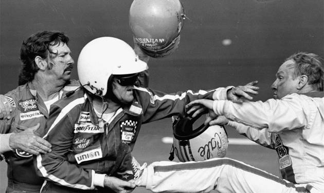 """FILE - In this Feb. 18, 1979 file photo, Bobby Allison holds race driver Cale Yarborough's foot after Yarborough kicked him following an incident on the final lap final lap of the Daytona 500 in Daytona Beach, Fla. NASCAR added a rule Friday, Aug. 15, 2014, ordering drivers to not approach the track or moving cars after accidents. """"Really, we're formalizing rules that have been there,"""" Robin Pemberton, NASCAR's vice president of competition and racing development, said at Michigan International Speedway. """"It's reminders that take place during drivers meetings with drivers about on-track accidents. (AP Photo/Ric Feld, File)"""