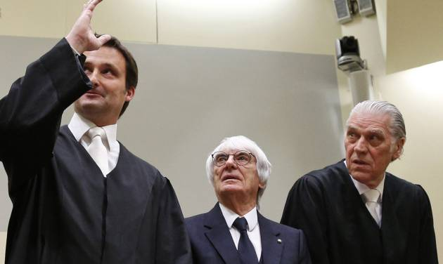 """Formula One boss Bernie Ecclestone stands between his lawyers Sven Thomas, right, and Norbert Scharf  after he arrived in the regional court in  Munich, Germany, Thursday, April 24, 2014. Ecclestone is charged with bribery and incitement to breach of trust """"in an especially grave case"""" over a US$ 44 million payment to a German banker, that prosecutors allege was meant to facilitate the sale of the Formula One Group to a buyer of Ecclestone's liking. (AP Photo/Matthias Schrader, pool)"""