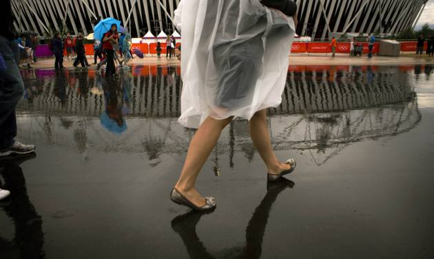Visitors walk during raining at the Olympic Park during the 2012 Summer Olympics, Sunday, July 29, 2012, in London. (AP Photo/Emilio Morenatti)