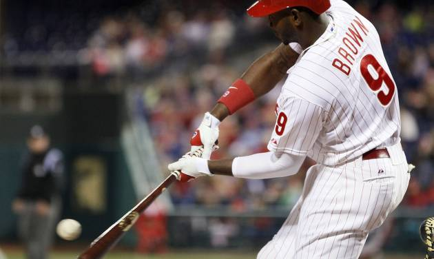 Philadelphia Phillies' Domonic Brown connects for a single to load the bases  during the fifth inning of a baseball game against the Miami Marlins, Friday, April 11, 2014, in Philadelphia. (AP Photo/Tom Mihalek)