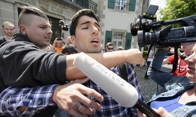 Uruguay's soccer player Luis Suarez leaves the international Court of Arbitration for Sport, CAS, surrounded by fans and media after a five hour hearing in Lausanne, Switzerland, Friday, Aug. 8, 2014. Suarez appealed to the CAS against the four-month ban imposed by FIFA on the Uruguay striker. Suarez was banned for biting Italy's Giorgio Chiellini at the FIFA Brazil 2014 World Cup. (AP Photo/Keystone, Laurent Gillieron)