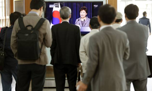 People watch a live television program showing South Korean President Park Geun-hye's speech to the nation regarding the sunken ferry Sewol at the Seoul Train Station in Seoul, South Korea, Monday, May 19, 2014. South Korea's president said Monday she will push to disband the coast guard in the wake of last month's ferry disaster that left more than 300 people dead or missing, calling its rescue operations after the disaster a failure. (AP Photo/Lee Jin-man)