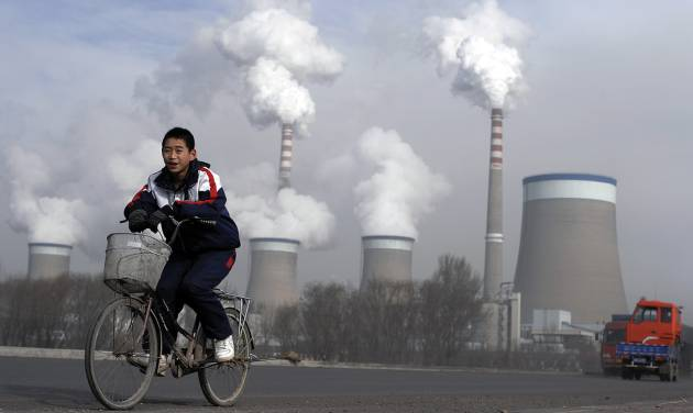 FILE - In this Dec. 3, 2009 file photo, a Chinese boy cycles past a cooling towers of a coal-fired power plant in Dadong, Shanxi province, China. President Barack Obama's proposal to curb U.S. greenhouse gas emissions might improve the chances of completing a global climate treaty but is unlikely to defuse demands by China, India and others for Americans to do more. China, the biggest emitter, has promised to curb its output but with its economy slowing, and communist leaders under pressure to generate jobs, has resisted binding limits. (AP Photo/Andy Wong, File)