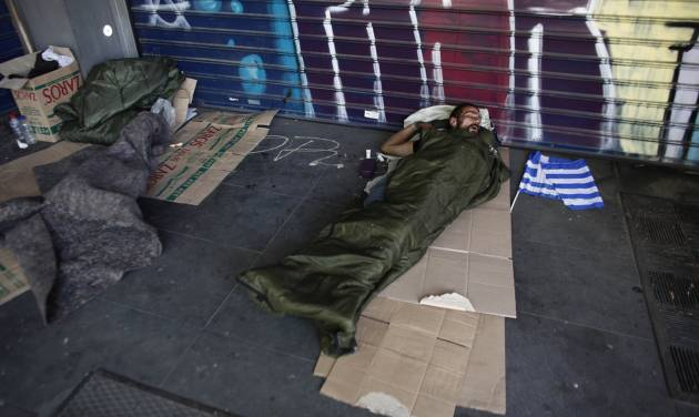 A homeless man sleeps on a sidewalk beside a small Greek flag, carried from a party political rally, by his side, in Athens, Saturday May 5, 2012. Greece goes to early polls Sunday while in the throes of a deep financial crisis. No single party is expected to win an overall majority in the 300-member Greek parliament. (AP Photo/Kostas Tsironis)