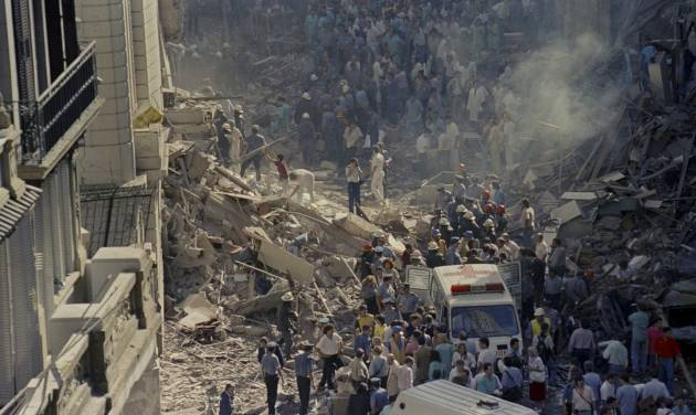 In this March 17, 1992 file photo, firemen and rescue workers walk through the debris of Israel's Embassy after a terrorist attack in Buenos Aires, Argentina. Israel summoned the Argentinian ambassador on Tuesday Jan. 29, 2013 in protest over an agreement between Iran and Argentina to jointly investigate the terror bombing 19 years ago of a Jewish center that killed 85 people in Buenos Aires and that was widely blamed on Tehran. (AP Photo/Don Rypka, File )