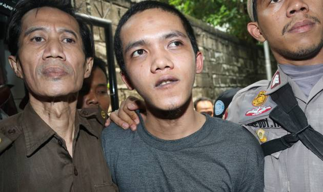 Child sexual abuse suspect Agun Iskandar, center, is escorted by security officers upon arrival for his trial at district court in Jakarta, Indonesia, Tuesday, Aug. 26, 2014. The first of five janitors accused of raping a kindergartner in a bathroom at a prestigious international school went on trial Tuesday. (AP Photo/Tatan Syuflana)