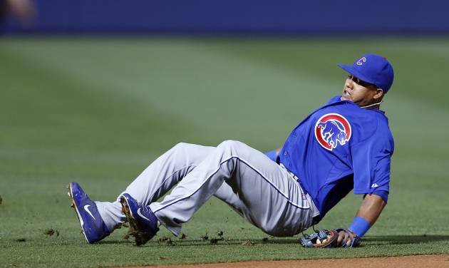 Chicago Cubs shortstop Starlin Castro slips as he attempts to field a ground ball hit by Atlanta Braves' Chris Johnson in the first inning of a baseball game on Friday, May 9, 2014, in Atlanta. Johnson was credited with a base hit. (AP Photo/John Bazemore)