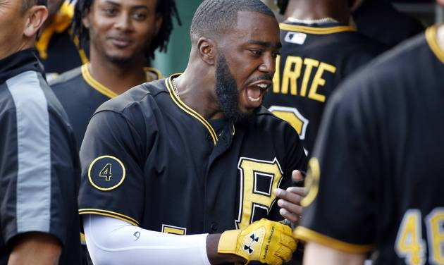 Pittsburgh Pirates' Josh Harrison, center, celebrates with teammates after scoring on a single by Pirates' Gregory Polanco off San Diego Padres starting pitcher Ian Kennedy during the first inning of a baseball game in Pittsburgh, Friday, Aug. 8, 2014. (AP Photo/Gene J. Puskar)
