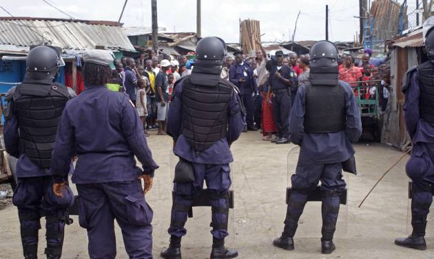 Liberian security forces with riot gear stop people from leaving the West Point area, that has been hardest hit by the Ebola virus spreading in Monrovia, Liberia, Monday, Aug. 25, 2014. A Liberian doctor who was among three Africans to receive an experimental Ebola drug has died, the country's information minister said Monday.(AP Photo/Abbas Dulleh)