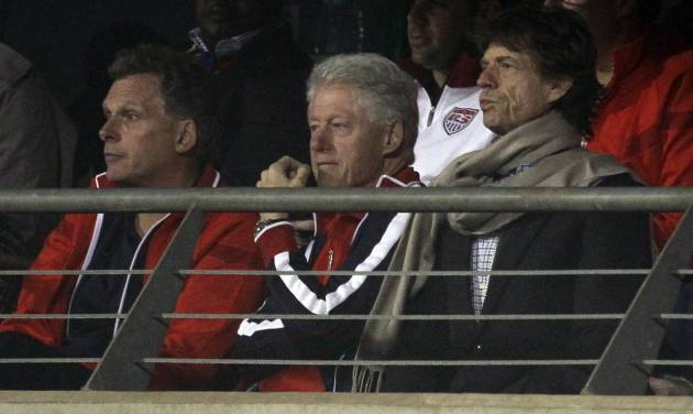 FILE - In this  June 26, 2010, file photo, Terence McAuliffe, former chairman of the Democratic National Committee, left, former U.S. President Bill Clinton, center, and rock star Mick Jagger, right, watch the World Cup round of 16 soccer match between the United States and Ghana at Royal Bafokeng Stadium in Rustenburg, South Africa.  Earlier in that tournament, Jagger had already earned a reputation for losing picks by showing up in the stands with Bill Clinton to cheer on the United States, which lost to Ghana in the second round, and then a day later watched as England was trounced by Germany 4-1. (AP Photo/Matt Dunham, File)