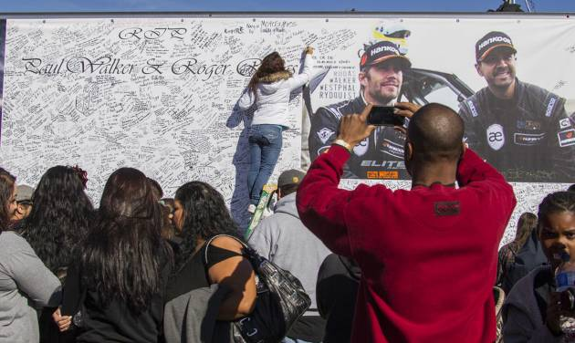 FILE - In this Dec. 8, 2013 file photo, fans crowd the scene of a memorial rally and car cruise in Valencia, Calif., to remember actor Paul Walker and his friend Roger Rodas, who died in a fiery car crash. The wife of Rodas, who was driving the car that crashed and killed him and Walker, sued Porsche in Los Angeles Superior Court on Monday, May 12, 2014, alleging the sports car malfunctioned and caused the accident. (AP Photo/Ringo H.W. Chiu, file)