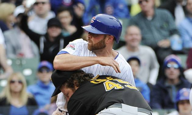 Chicago Cubs' Nate Schierholtz, top, scores on a wild pitch as Pittsburgh Pirates starting pitcher Gerrit Cole (45) makes a late tag during the fourth inning of a baseball game on Thursday, April 10, 2014 in Chicago. (AP Photo/David Banks)