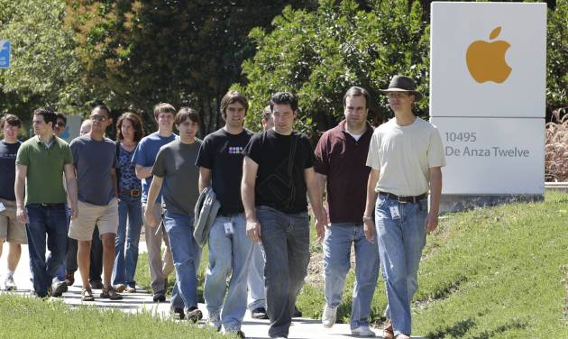 FILE - In this Aug. 25, 2011 file photo, Apple employees walk between buildings at Apple headquarters in Cupertino, Calif. A breakdown released Tuesday, Aug. 12, 2014 by Apple Inc. showed 54 percent of the company's technology jobs in the U.S. are handled by whites and another 23 percent by Asians. Men make up 80 percent of Apple's technology workforce throughout the world. (AP Photo/Paul Sakuma, File)