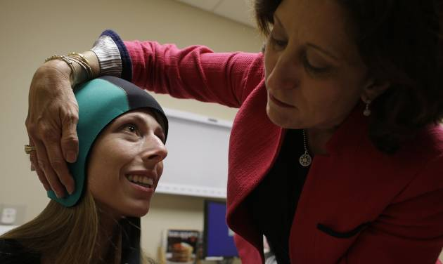 In this Wednesday, July 10, 2013, photo, Dr. Hope Rugo, right, an oncologist and breast cancer specialist, demonstrates the use of the Dignitana DigniCap system on Katherine Serrurier, a research assistant and pre-medical intern, at the University of California San Francisco Mount Zion Hospital cancer center in San Francisco. The caps chill the head and scalp allowing for hair preservation in chemo treatments. (AP Photo/Eric Risberg)