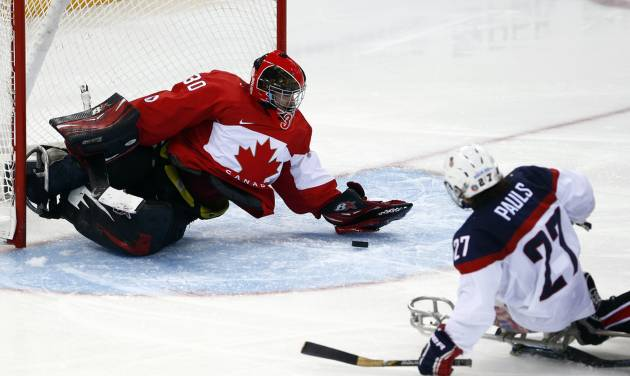 United States' Joshua Pauls, right, shoots on goal as Canada's goaltender Corbin Watson tries to defend during the ice sledge hockey semifinal match at the 2014 Winter Paralympics in Sochi, Russia, Thursday March 13, 2014. United States won 3-0. (AP Photo/Pavel Golovkin)