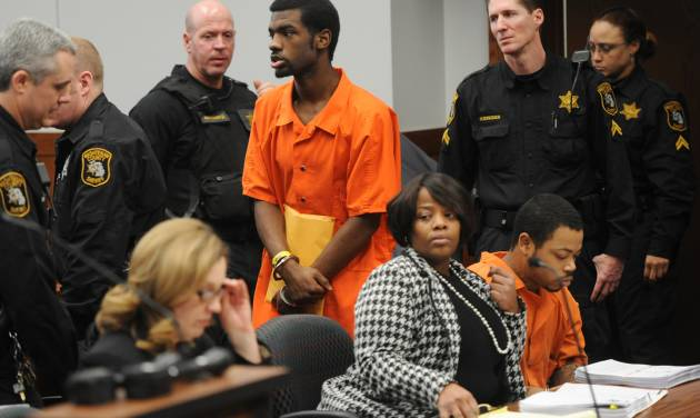 FILE - In this Jan. 17, 2014 file photo, Ed Thomas walks past Kristopher Pratt as he enters the courtroom for their preliminary hearing at District Court in Pittsfield Township, Mich. Pratt, 19 and Thomas, 20 are accused in the fatal shooting of Demarius Reed, an Eastern Michigan University football player. Reed was found shot in the stairwell at his off-campus apartment building in October of 2013. Pratt and Ed Thomas are to appear Tuesday, July 1, 2014 in Washtenaw County Trial Court for a final hearing before they stand trial later this month. (AP Photo/The Ann Arbor News, Melanie Maxwell)