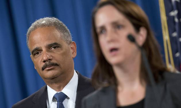 Attorney General Eric Holder listens at left during a news conference at the Justice Department in Washington, Thursday, Sept. 4, 2014, to announce the Justice Department's civil rights division will launch a broad civil rights investigation in the Ferguson, Mo., Police Department. At right is Acting Assistant Attorney General for Civil Rights Division Molly Moran. (AP Photo/Pablo Martinez Monsivais)