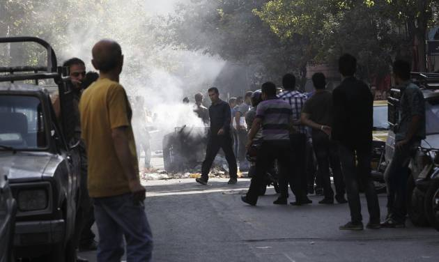This photo, taken by an individual not employed by the Associated Press and obtained by the AP outside Iran shows, Iranians stand in a street as a garbage can is set on fire, in central Tehran, near Tehran's old main bazaar, on Wednesday, Oct. 3, 2012. Police threatened merchants who closed their shops in Tehran's main bazaar and launched crackdowns on sidewalk money changers on Wednesday as part of a push to halt the plunge of Iran's currency, which has shed more than a third its value in less than a week. (AP Photo) EDITORS NOTE AS A RESULT OF AN OFFICIAL IRANIAN GOVERNMENT BAN ON FOREIGN MEDIA COVERING SOME EVENTS IN IRAN, THE AP WAS PREVENTED FROM INDEPENDENT ACCESS TO THIS EVENT.
