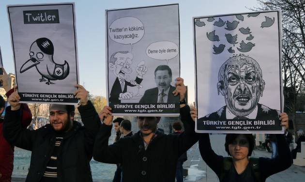 """Members of the Turkish Youth Union hold cartoons depicting Turkey's Prime Minister Recep Tayyip Erdogan during a protest against a ban on Twitter, in Ankara, Turkey, Friday, March 21, 2014. Turkey's attempt to block access to Twitter appeared to backfire on Friday with many tech-savvy users circumventing the ban and suspicions growing that the prime minister was using court orders to suppress corruption allegations against him and his government. Cartoon in center reads: Erdogan, left, to his Ankara Mayor Melih Gokcek """" we will rip out the roots of Twitter."""" Gokcek: """"don't say it."""" (AP Photo/Burhan Ozbilici)"""