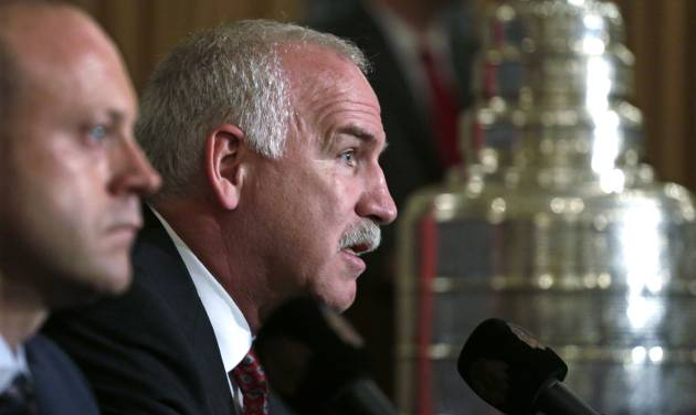 Chicago Blackhawks coach Joel Quenneville, right, speaks during a news conference Friday, July 26, 2013 in Chicago, accompanied by Vice President/General Manager Stan Bowman. The Blackhawks announced an agreement that will keep the two-time Stanley Cup winning head coach with the team through through the end of the 2016-17 National Hockey League season. (AP Photo/M. Spencer Green)