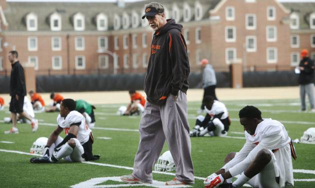 "Oklahoma State defensive coordinator Glenn Spencer walks through rows of players stretching during practice on Tuesday, April 1, 2014 at the outside fields of the Sherman E. Smith training facility of Oklahoma State University in Stillwater. The Cowboys' will hold ""Orange Blitz"", an open practice that will replace the annual spring game this Saturday. Photo by KT King/For the Oklahoman"