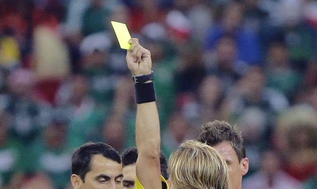 Referee Ravshan Irmatov of Uzbekistan gives a yellow card to Croatia's Ivan Rakitic during the group A World Cup soccer match between Croatia and Mexico at the Arena Pernambuco in Recife, Brazil, Monday, June 23, 2014. (AP Photo/Sergei Grits)