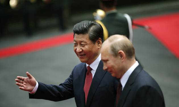 Russia's President Vladimir Putin, right, and China's President Xi Jinping review an honor guard during a welcome ceremony at the Xijiao State Guesthouse ahead of the fourth Conference on Interaction and Confidence Building Measures in Asia (CICA) summit, in Shanghai, China, Tuesday, May 20, 2014. (AP Photo/Carlos Barria, Pool)