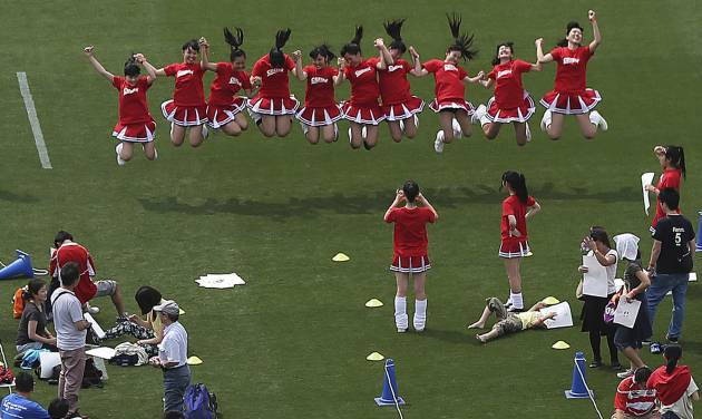 The volunteers jump to take a photo on the pitch during an event at the National Stadium in Tokyo, Sunday, May 25, 2014. Tokyo's National Stadium, the centerpiece of the 1964 Summer Olympics, hosted its final sporting event on Sunday before it will be demolished to make way for a new 80,000-seat structure that will be the main venue of the 2020 Olympics. (AP Photo/Eugene Hoshiko)
