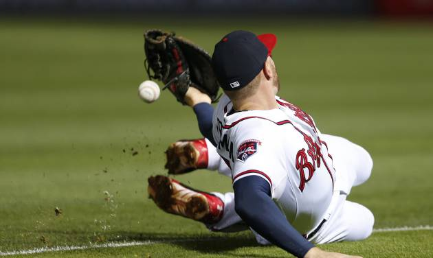 Atlanta Braves first baseman Freddie Freeman can't reach an RBI single by Boston Red Sox's Jonny Gomes in the seventh inning of a baseball game Tuesday, May 27, 2014, in Atlanta. (AP Photo/John Bazemore)