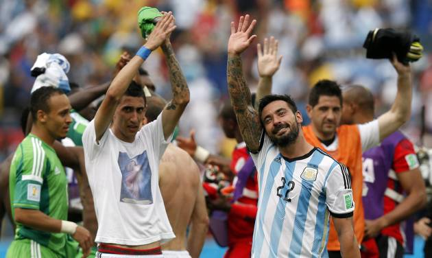 Argentina's Angel di Maria, left, and Ezequiel Lavezzi wave to spectators after their 3-2 win over Nigeria in the group F World Cup soccer match between Nigeria and Argentina at the Estadio Beira-Rio in Porto Alegre, Brazil, Wednesday, June 25, 2014. (AP Photo/Victor R. Caivano)
