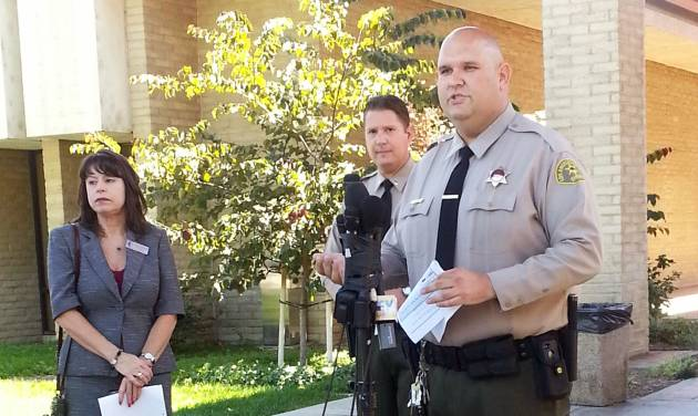 Santa Clarita Valley Sheriff's Station deputy Joshua Dubin announces the arrest of a 15-year-old boy Sunday, Aug. 17, 2014, on suspicion of posting online threats to shoot students at Southern California schools in Valencia, Calif. Deputies arrested the teen after serving a search warrant at his home, Lt. Tom Bryski said. (AP Photo/The Santa Clarita Valley Signal, Kristine Alfaro)