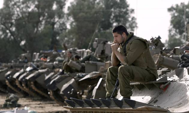 Israeli soldiers with armored vehicles gather in a staging ground near the border with Gaza Strip, southern Israel, Friday, Nov. 16, 2012. Fierce clashes between Israeli forces and Gaza militants are continuing for the third day.(AP Photo/Tsafrir Abayov)