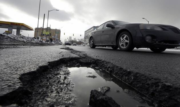 FILE - This Feb. 11, 2014 file photo shows a car driving by a pothole in Detroit, as a fuel station is seen in the background. Congress has kept federal highway and transit programs limping along for the past six years, unable to decide how best to pay for them. Lawmakers' indecision mirrors what The Associated Press and GfK found in a recent opinion survey. (AP Photo/Carlos Osorio, File)