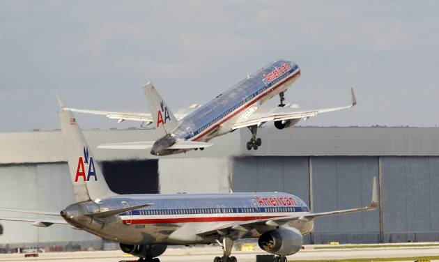 In this Thursday, Oct. 11, 2012 photo, an American Airlines Boeing 757 passenger jet takes off as another waits on the taxiway at Miami International Airport in Miami. Directors of American Airlines' parent company likely won't make a decision when they meet Wednesday, Jan 9, 2013, to consider a possible merger with US Airways, even as momentum for a deal is building. Investors have been bidding up US Airways' stock price, and leaders of the two pilot unions agree on how to combine contracts, two developments that analysts say strengthen the case for a tie-up. (AP Photo/Wilfredo Lee)
