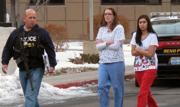 Police escort hospital staff away from a medical office building in Reno, Nev., on Tuesday, Dec. 17, 2013. A suicidal gunman killed one person and critically wounded two others before turning the gun on himself on the grounds of Renown Regional Medical Center Tuesday. (AP Photo/Scott Sonner).
