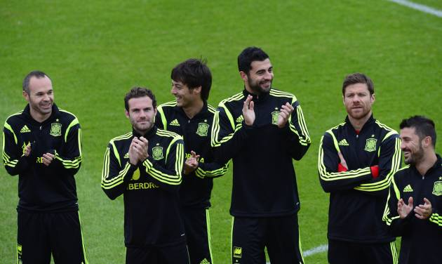 Spain's players, Andres Iniesta, from left to right, Juan Mata, David Silva, Raul Albiol, Xabi Alonso, and David Villa, applaud during a promotional event, before the start of a training session at the Atletico Paranaense training center in Curitiba, Brazil, Tuesday, June 10, 2014. Spain will play in group B of the Brazil 2014 World Cup. (AP Photo/Manu Fernandez)