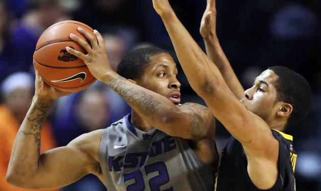 Kansas State guard Rodney McGruder (22) is covered by West Virginia guard Gary Browne (14) during the first half of an NCAA college basketball game in Manhattan, Kan., Monday, Feb. 18, 2013. (AP Photo/Orlin Wagner)