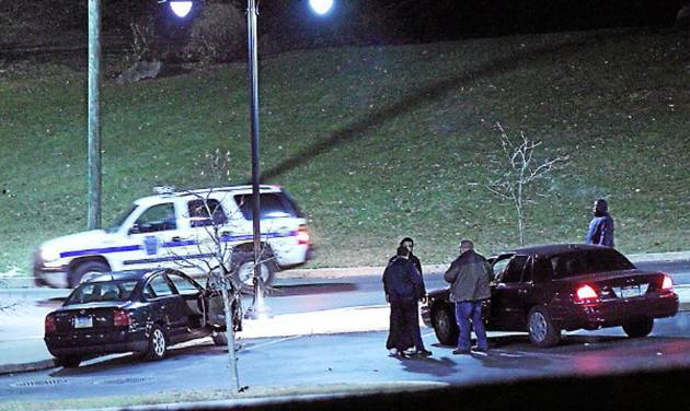 Police investigate a car, left, at the athletic center of Widener University in Chester, Pa. after a student was shot Monday, Jan. 20, 2014. Authorities warned students to remain indoors until further notice. (AP Photo/Delaware County Daily Times, Robert J. Gurecki)  PHILLY METRO OUT