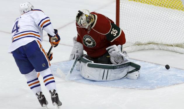 Edmonton Oilers left wing Taylor Hall (4) scores on Minnesota Wild goalie Darcy Kuemper during tje shootout of in NHL hockey game in St. Paul, Minn., Tuesday, March 11, 2014. Edmonton won 4-3. (AP Photo/Ann Heisenfelt)