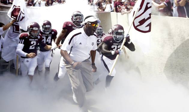 Texas A&M coach Kevin Sumlin, center, leads his team out onto the field before an NCAA college football game against Florida, Saturday, Sept. 8, 2012, in College Station, Texas. Texas A&M begins a new era with its first Southeastern Conference game after leaving the Big 12 Conference. (AP Photo/David J. Phillip)