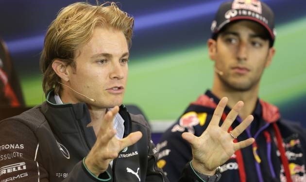 Red Bull driver Daniel Ricciardo of Australia, right, looks at Mercedes driver Nico Rosberg of Germany, as he addresses the media ahead of Sunday's Belgian Formula One Grand Prix in Spa-Francorchamps, Belgium, Thursday, Aug. 21, 2014. (AP Photo/Yves Logghe)