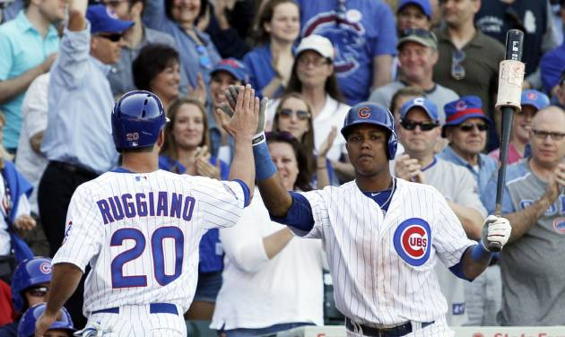 Chicago Cubs' Justin Ruggiano (20) celebrates with Starlin Castro after scoring on a two-run double hit by Anthony Rizzo during the eighth inning of a baseball game against the Miami Marlins in Chicago, Friday, June 6, 2014. (AP Photo/Nam Y. Huh)