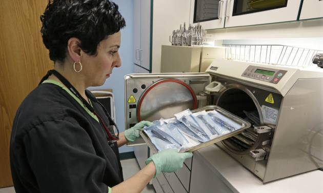 "Dentist Alice G. Boghosian removes packages of properly sterilized dental instruments from an autoclave that uses heat and steam to sterilize the tools Friday, March 29, 2013, in Chicago. Health officials in Oklahoma are calling an oral surgeon there who used dirty equipment and risked cross-contamination a ""menace to public health"" and are urging thousands of his patients to seek medical screenings for hepatitis B, hepatitis C and HIV. Though officials say such situations involving dental clinics are rare, Dr. Matt Messina, a dentist in Cleveland, and a consumer advisor for the American Dental Association, says patients should ask their dentist and oral surgeon about the steps they and their staffs take to sterilize equipment. (AP Photo/M. Spencer Green)"