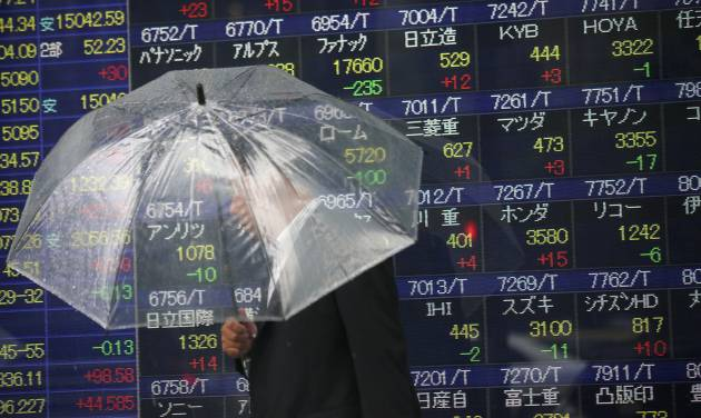 FILE - In this June 6, 2014 file photo, a man holding an umbrella walks past an electronic stock indicator of a securities firm, in Tokyo. The Treasury Department releases foreign holdings data for April on Monday, June 16, 2014. (AP Photo/Eugene Hoshiko, File)