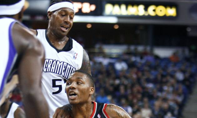 Portland Trail Blazers guard Damian Lillard, right, drives to the basket around Sacramento Kings defender James Johnson during the first half of an NBA basketball game in Sacramento, Calif., on Sunday, Dec. 23, 2012. (AP Photo/Steve Yeater)
