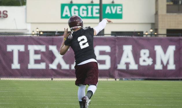 Texas A&M quarterback Johnny Manziel warms up with teammates on the first day of fall practice in College Station, Texas, Monday, Aug. 5, 2013.  (AP Photo/Bryan College Station Eagle, Stuart Villanueva)