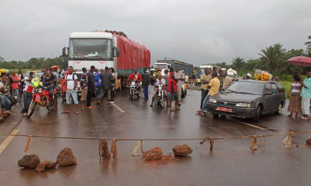 In this photo taken on Tuesday, Aug. 12,  2014, stranded people stand behind a  rope across the road that separates Guinea and Sierra Leone, and works as a makeshift border control checkpoint at Gbalamuya-Pamelap, Guinea. As Guinea closed its border with Sierra Leone at the weekend in an attempt to halt the spread of the deadly Ebola virus, people and goods were not able to cross to either side.  (AP Photo/ Youssouf Bah)