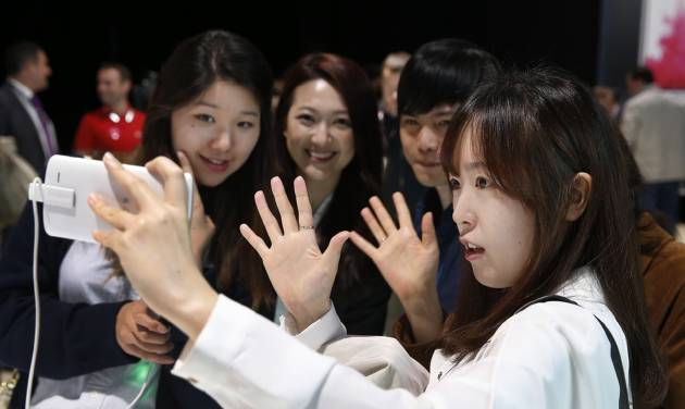People pose for a selfie using LG's newly unveiled smartphone called the G3 at a press event in London, Tuesday, May 27, 2014. (AP Photo/Lefteris Pitarakis)
