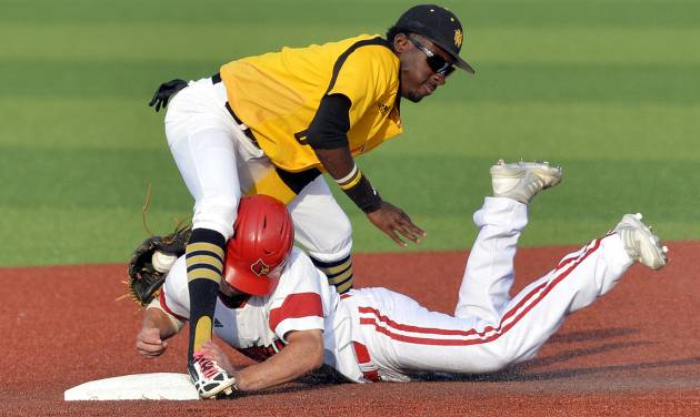 Kennesaw State's Cornell Nixon, top, tags Louisville's Nick Solak out as he attempted to steal second base in the third inning of an NCAA college baseball tournament super regional game in Louisville, Ky., Friday, June 6, 2014. (AP Photo/Timothy D. Easley)