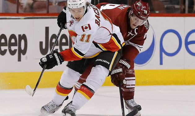 Calgary Flames' Mikael Backlund (11) battles Phoenix Coyotes' Shane Doan for the puck during the first period of an NHL hockey game on Saturday, March 15, 2014, in Glendale, Ariz. (AP Photo/Matt York)